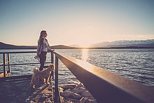 Frau am See bei Sonnenuntergang mit ihrem Hund