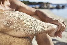 Sandiger Unterarm eines Mannes, der sich am Strand entspannt, Nahaufnahme