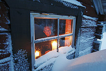 Mann sucht durch Fenster der Blockhütte