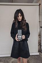 Dunkelhaarige junge Frau mit Vintage-Kamera im Studio