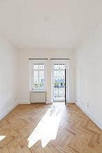 Leeres Zimmer mit Fischgrätparkett und geöffneter Balkontür