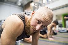 Porträt eines jungen Mannes, der im Fitnessstudio trainiert.