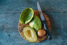 Geschnittene Avocado, Kern und Messer auf Holzplatte