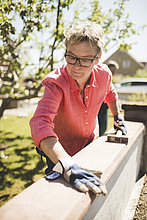 Seniorenfrauen bei der Untersuchung von Holzbrettern an der Hofmauer