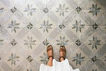 Frau auf kunstvollem Fliesenboden stehend