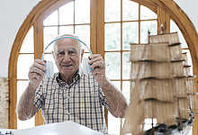 Porträt des selbstbewussten Senioren beim Auspacken von Kopfhörern aus dem Paket mit Schiffsmodell auf dem Tisch