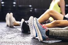 Füße von Sportlern, die in der Turnhalle auf dem Boden sitzen