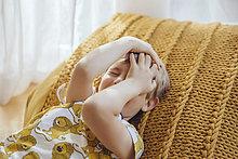 Kleiner Junge, der mit den Händen auf dem Kissen liegt.