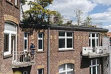 Frau steht auf dem Balkon des Backsteinhauses