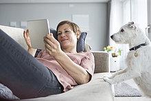 Porträt einer lächelnden Frau, die auf der Couch liegt und dabei den Hund beobachtet.