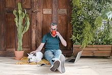 Der bärtige Mann sitzt mit seinem Hund auf dem Boden zu Hause und trinkt Kaffee.