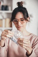 Frau betrachtet Plastiktüte mit Werkzeugen und Schrauben für die Möbelmontage