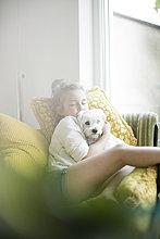 Kleines Mädchen sitzt auf einem Sessel zu Hause und kuschelt mit ihrem Hund.