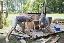 Männliche Freunde beim Zusammenbau des Holzdecks um den Whirlpool im Hof