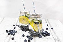 Zwei Gläser aufgegossenes Wasser mit Zitronenscheiben, Heidelbeeren und Minze