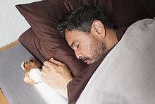 Hochwinkelansicht des erwachsenen Mannes, der von einem kleinen Teddybären auf dem Bett zu Hause schläft.