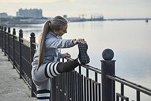 Seitenansicht einer Athletin, die sich auf dem Fußweg auf dem Geländer ausdehnt, Blagoveshchensk, Amur, Russland