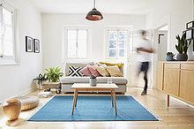 Mann, der in einem hellen, modernen Wohnzimmer in einem alten Landhaus spazieren geht.
