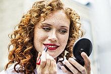 Porträt einer sommersprossigen jungen Frau mit Lippenstift