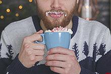 Mann trinkt heiße Schokolade mit Schlagsahne und gehackten Zuckerstangen zur Weihnachtszeit