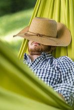 Mann entspannt in der Hängematte mit Hut im Gesicht