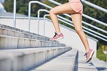 Nahaufnahme einer Frau, die auf einer Treppe läuft.