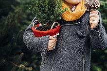 Fröhlicher Junge bereitet sich auf Weihnachten vor, hält Topfbaum, isst Schokolade getauchten Apfel