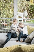 Portrait von zwei Mädchen mit Hund auf Couch im Wohnzimmer
