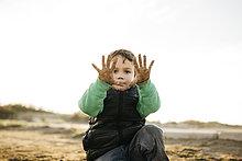 Junge, der im Winter am Strand spielt und seine schmutzigen Hände zeigt.