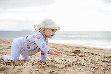 Spanien, Lanzarote, kleines Mädchen, das am Strand krabbelt