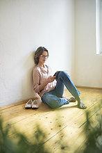 Reife Frau auf dem Boden sitzend mit Tablette