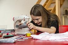 Lächelndes Mädchen mit Nähmaschine