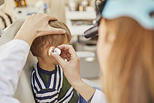 HNO-Arzt untersucht Ohr eines Jungen