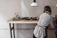 Rückansicht der Unternehmerin am Tisch mit Essteller an der Wand in der Werkstatt