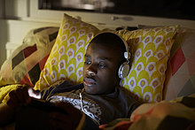 Nahaufnahme eines Jungen mit Kopfhörer über ein digitales Tablett, während er zu Hause auf dem Bett liegt.