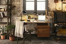 Alter Schreibtisch mit Laptop im Loft